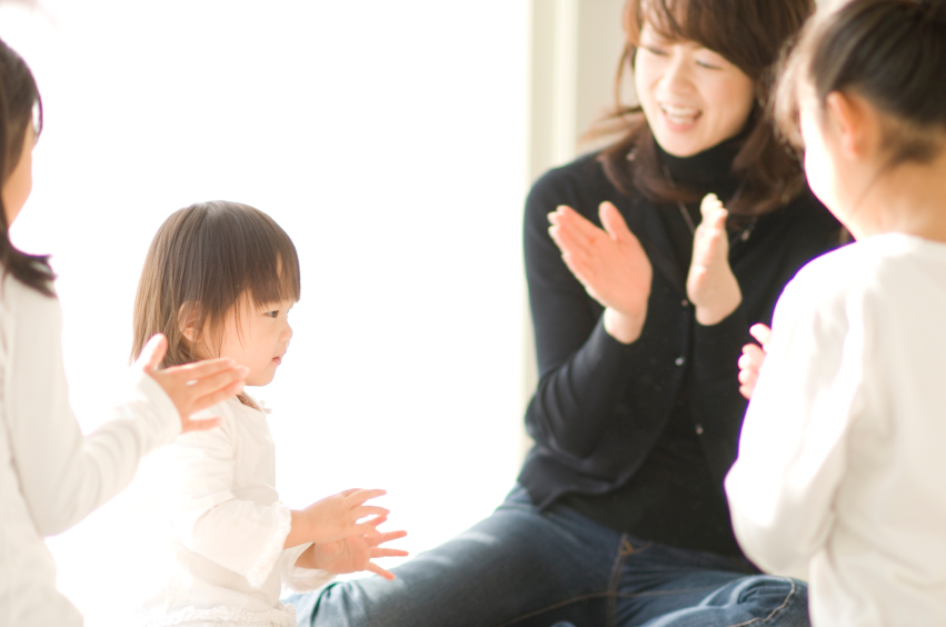 Three Japanese sisters and mother clapping their hands and playing