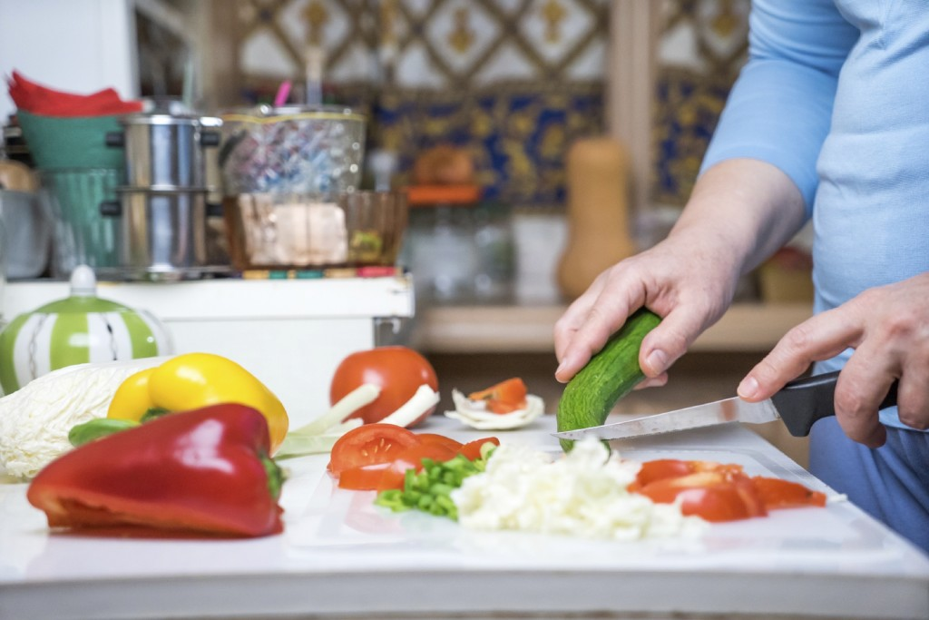 Cosy kitchen interior with fresh vegetables on table with female hands cooking